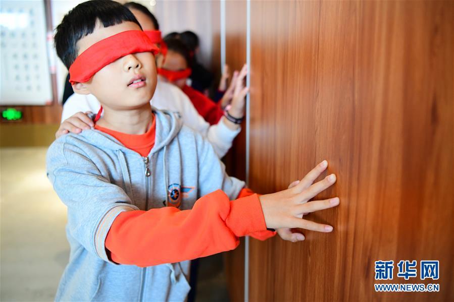 视障阅读区,小学生们将双眼蒙住体验在黑暗中行走. 新华社发(