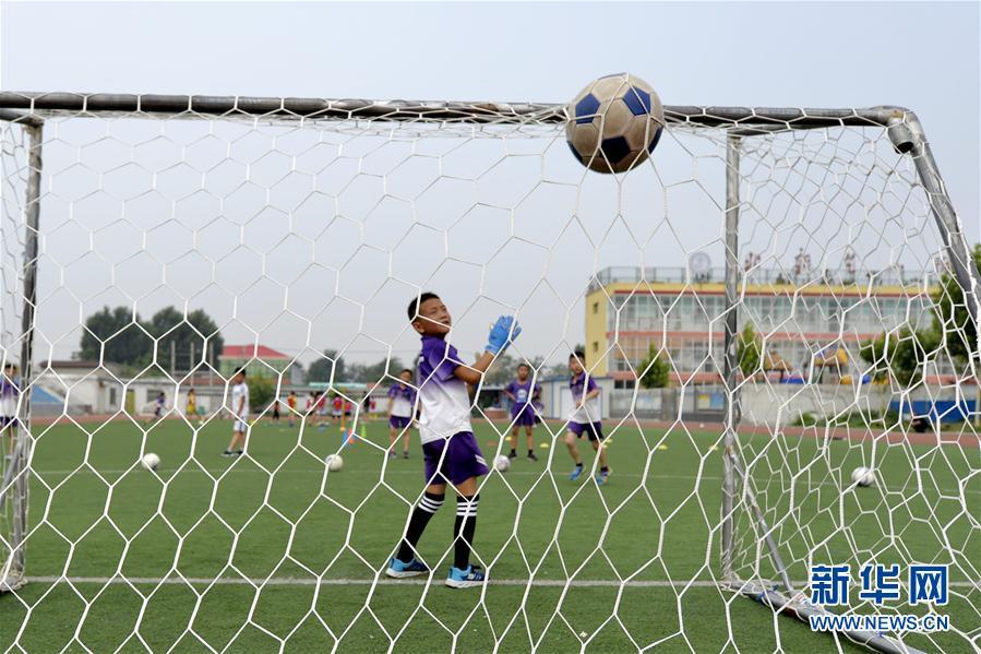 当日,宁晋县北新艺术小学热爱足球的学生在校园足球场进行足球基本
