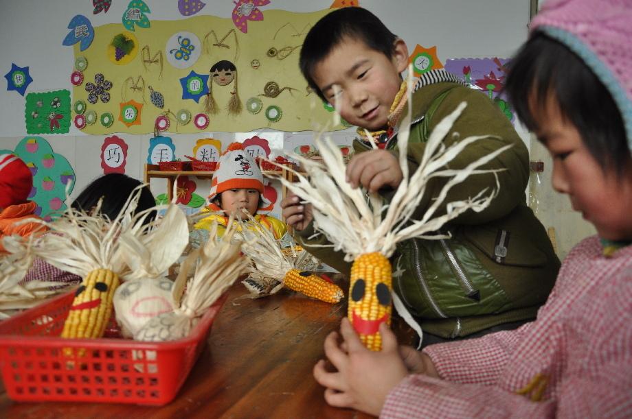 """望都县八里庄村幼儿园的幼儿正在动手制作""""玉米娃娃"""""""